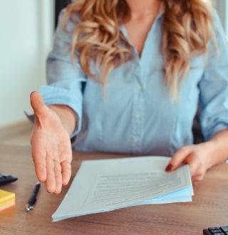 Vrouw achter een bureau steekt haar hand uit